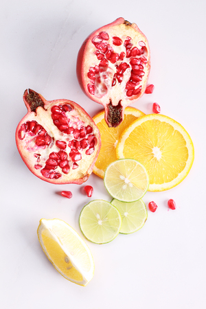 naranja color: red juicy pomegranate with citrus fruits on white background