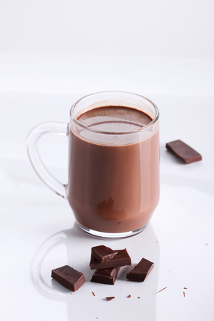 mug: hot chocolate drink in mug with chocolate pieces on white background
