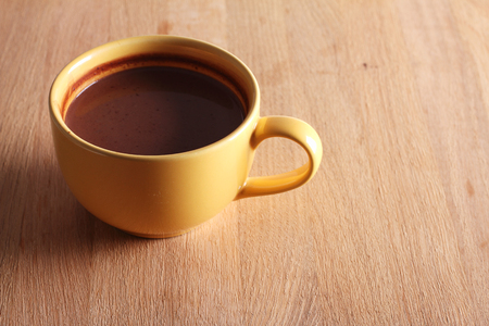 hot chocolate drink: hot chocolate drink in yellow cup on wooden background