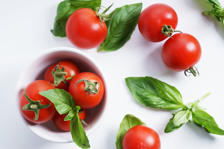 lycopene: Tomatoes. red ripe tomatoes and basil leaves.