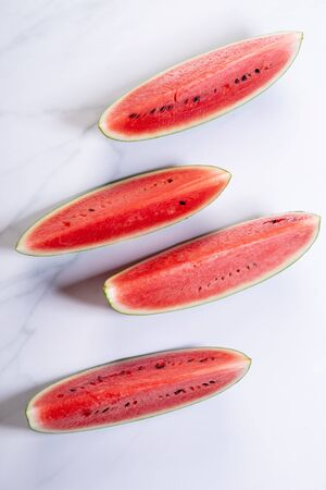 Slices of fresh watermelon on white marble background