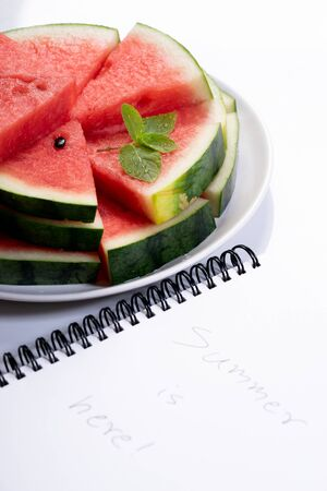 Slices of fresh watermelon with notebook paper on white marble background Stock Photo