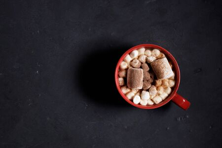 Red ceramic cups of hot cocoa with marshmallows on top of black rustic background Stock Photo