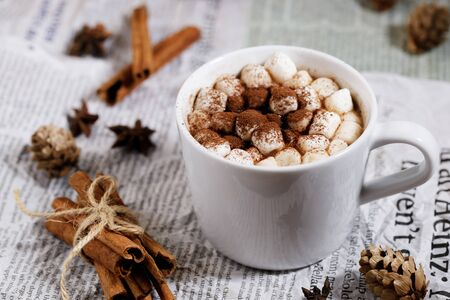 White ceramic cups of hot cocoa with marshmallows on top of rustic paper background