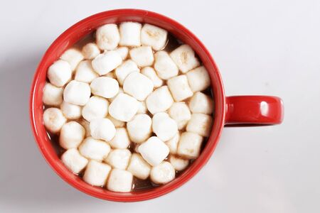 Red ceramic cups of hot cocoa with marshmallows on top of white marble background Stock Photo