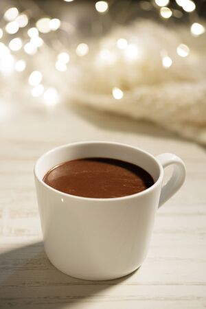 White ceramic cup of hot cocoa on white wooden background