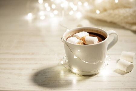 White ceramic cup of hot cocoa with marshmallows on white wooden background