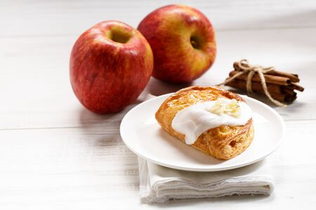 piece of cinnamon apple pie on a white plate with fresh apple in background, autumn food concept