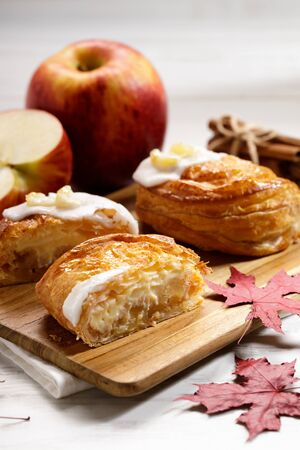 piece of cinnamon apple pie on a wooden board with fresh apple in background, autumn food concept