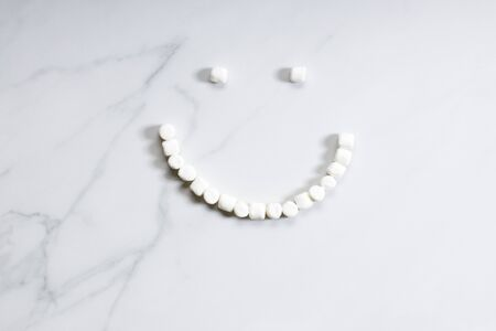 Smile-shaped marshmallows stopmotion on white marble background