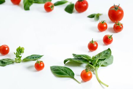 red cherry tomatoes on wooden background on white background on white background and basil leaf on white background Banque d'images