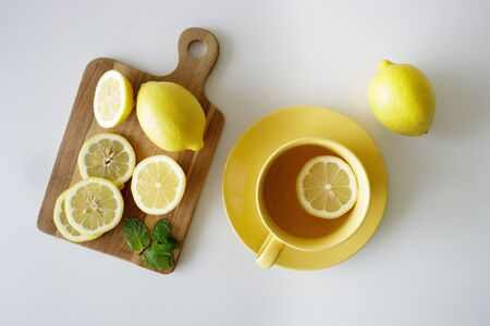 a cup of tea with fresh yellow lemons on white background