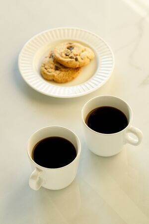 Two cups of coffees on white marble table in morning light