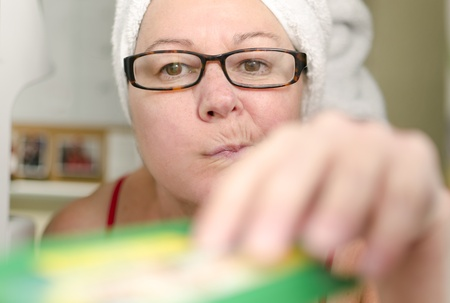overeat: A woman pulls a guilty face as she raids the refrigerator and cheats on her diet