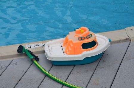 Toy boat and garden hose