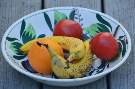 Orange,banana and tomatoes in a dish