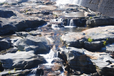 Water cascading down and around rocks Stock Photo