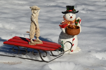 A girl on a sled with a snowman photo