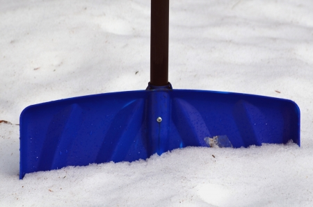 A blue snow shovel in the snow
