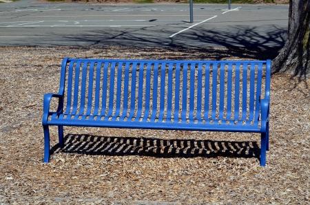 Blauwe bank in een park Stockfoto