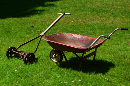 Antique push reel type lawn mower and wheelbarrow Stock Photo