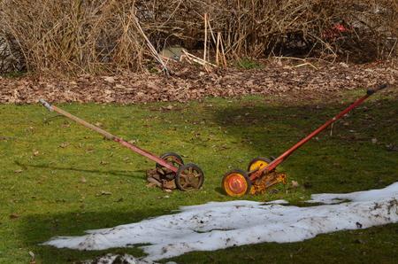 Two vintage push reel mowers outdoors in winter