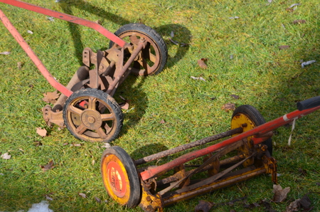 Two antique lawn mowers left outside