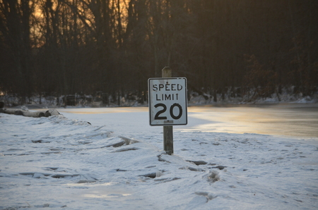 A speed limit sign stuck in a ice jam