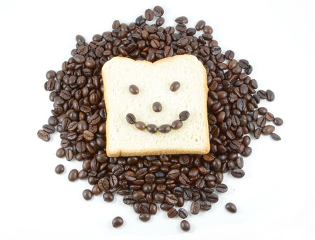 Coffee beans and the bread smiling on white background photo