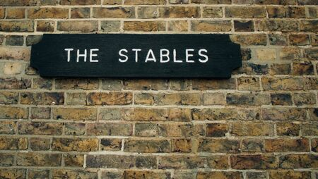 Plaque indicating The Stables in white lettering on black background attached to weathered brick wall