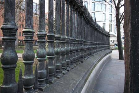10 March 2019 - London, UK: View along old metal railings in City of London