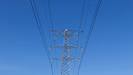 Geometric image of overhead power lines and pylon against blue sky
