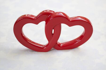 Two interconnected red ceramic hearts on white background with copyspace