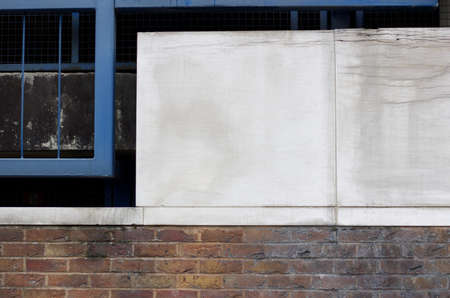 Grubby panelling above brick wall with metal frame to the side