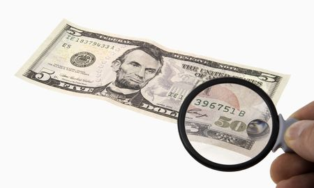 considers: The person considers a banknote through a magnifier Stock Photo