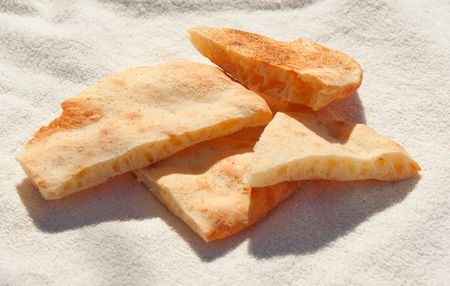 unleavened: Unleavened wheat cake pieces on a white fabric Stock Photo