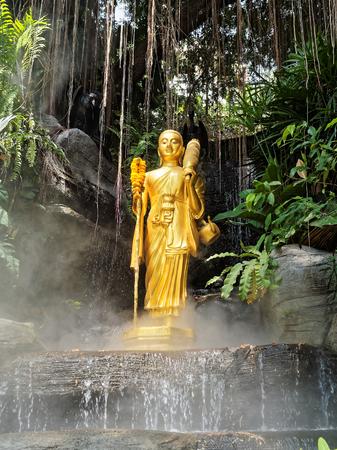 buddha statue: Buddha in the mist. A Buddha statue in a small waterfall. Stock Photo