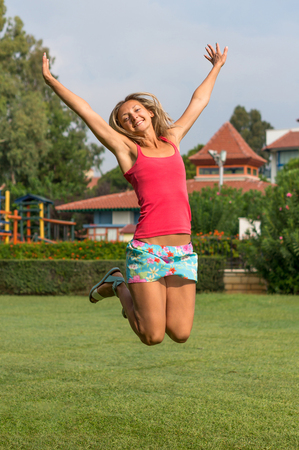 Attractive young smiling beautiful curly blonde hair slim girl fashion portrait in pink T-shirt  jumping in the field summer time green grass blue sky