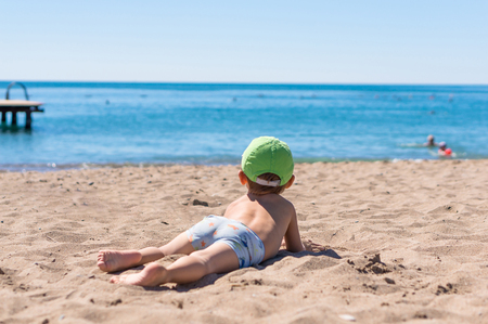 loose hair: Little baby boy sitting and playing with the sand Stock Photo