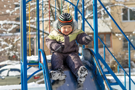Portrait of a happy little boy playing with a snow outdoor. Winter day. Happy family. Positive human emotions, feelings, joy. Active winter game. Stock Photo