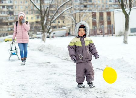 Portrait of beautiful toddler boy and his mother having fun in snowy park. Active winter game.