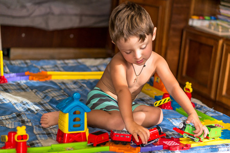Little blond kid boy is playing with plastic trains and railway indoor.