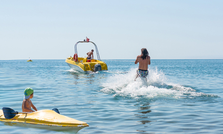 Young man glides on water skiing on the waves on the ocean. Healthy lifestyle. Positive human emotions. Smiling little baby boy in green baseball cap kayaking at tropical ocean sea in the day time. Foto de archivo