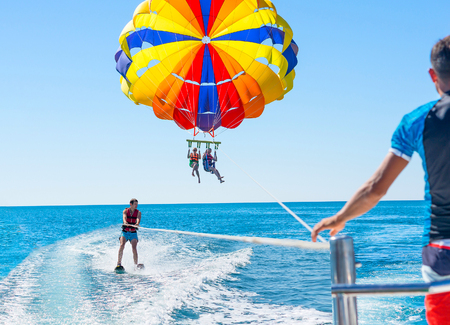 Happy couple Parasailing in Dominicana beach in summer. Couple under parachute hanging mid air. Positive human emotions, feelings, family. Young man glides on water skiing on the waves.Healthy lifestyle.