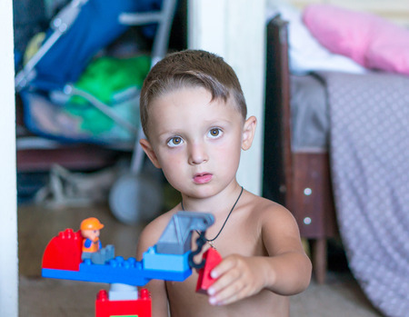 Little blond kid boy playing with lots of colorful plastic blocks indoor. Child having fun with building and creating.