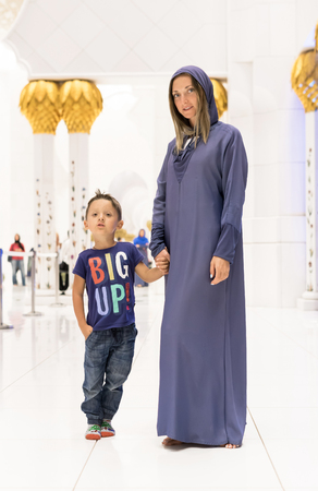 Woman with cute son dreaming at the grand mosque of Sheikh Zayed Mosque in Abu Dhabi wearing abaya, paranja in night time. Travelling.