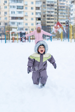 Portrait of beautiful smiling toddler boy and his mother having fun in snowy park. Active winter game. Happy family.