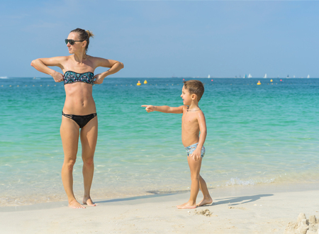Young mother in black sunglasses and smiling baby boy in green baseball cap playing in the sea in the day time. Positive human emotions, feelings, joy. Spring and summer holidays. Kisses and hugs Stock Photo - 92677208