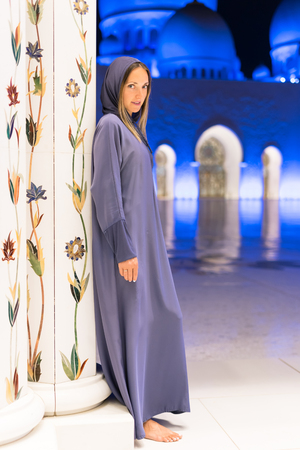 Woman dreaming at the grand mosque of Sheikh Zayed Mosque in Abu Dhabi wearing abaya, paranja in night time. Travelling. Stock Photo