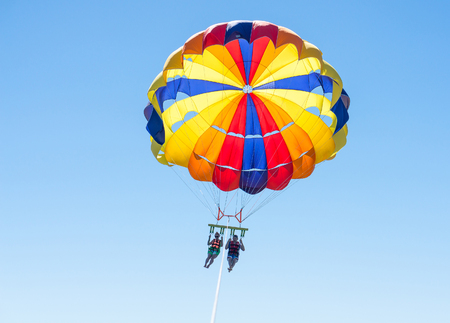 Happy couple Parasailing in Dominicana beach in summer. Couple under parachute hanging mid air. Having fun. Tropical Paradise. Positive human emotions, feelings, family, children, travel, vacation. Spring and summer holidays.